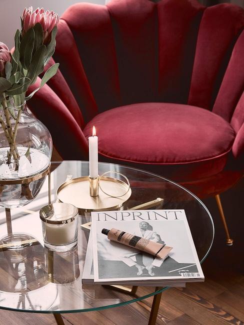 Aksamitne, czerwone krzesło w kształce muszli ze szklanym stolikiem oraz elementami dekoracyjnymi