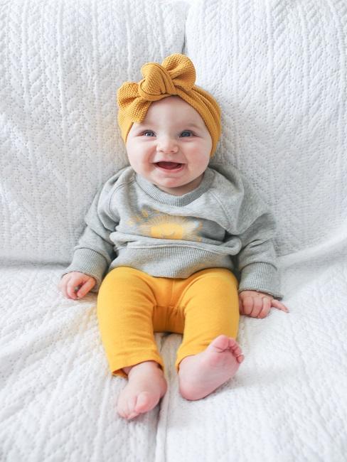 Baby auf einem Sofa, lachend