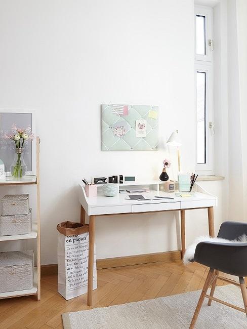 Bureau blanc avec pieds en bois, tapis crème et fauteuil noir