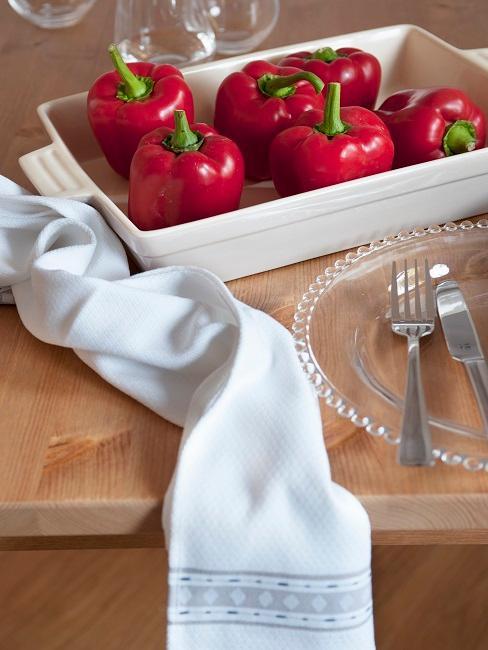 Rote Paprika auf einem gedeckten Esstisch