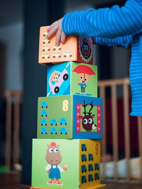 Zwei Kinderarme, die gerade einen Klotz auf mehrere andere zum Turm stellen