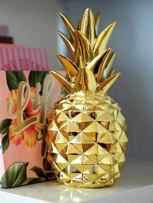 Goldfarbene Ananas als Buchstütze im Bücherregal