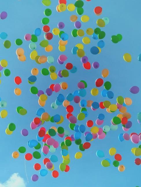 Ganz viele bunte Luftballons fliegen dem Himmel entgegen