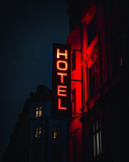 Hotel von außen bei Nacht mit leuchtend roter Schrift