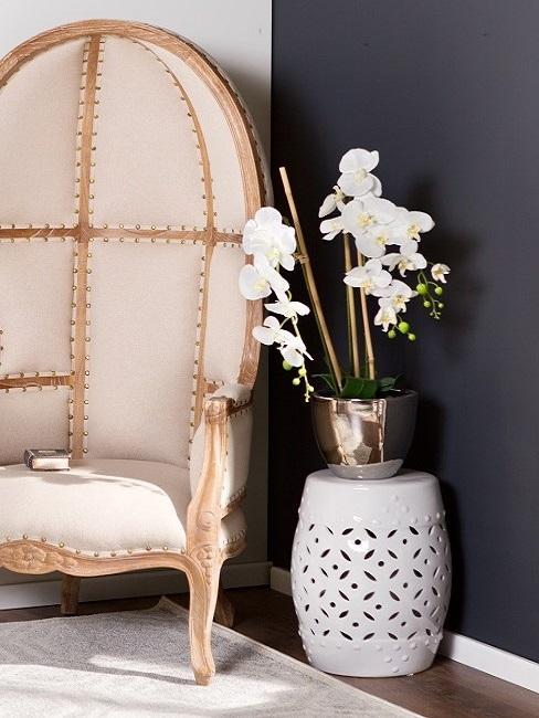 Decoración con orquídeas blancas sobre un taburete al lado de un sillón