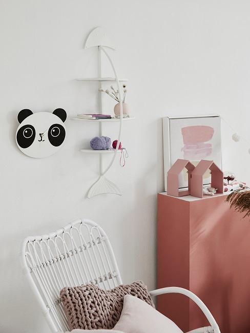 Mały pokój dziecięcy z białym fotelem bujanym, zegarem pandą i półką ścienną obok różowego kredensu
