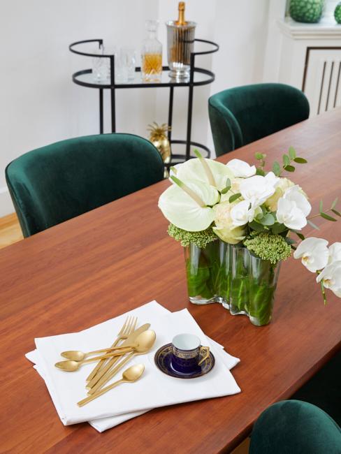Esszimmertisch mit Blumen und goldenem Besteck