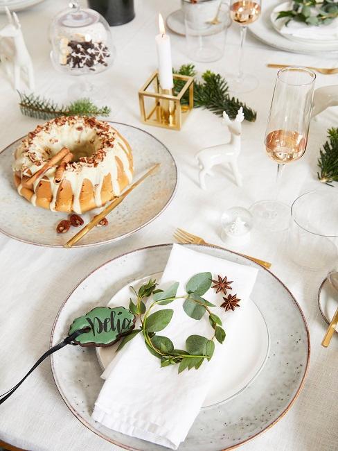 una mesa con decoración clara, con pastel y platos blancos