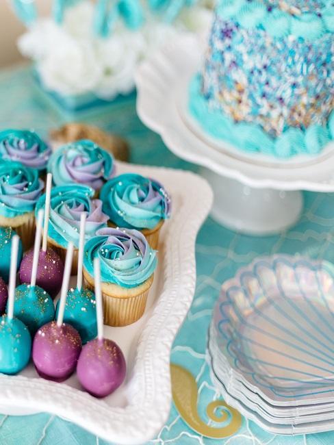 Décoration de table d'anniversaire de style sirène en turquoise avec des assiettes en coquillages et des desserts bleus et violets