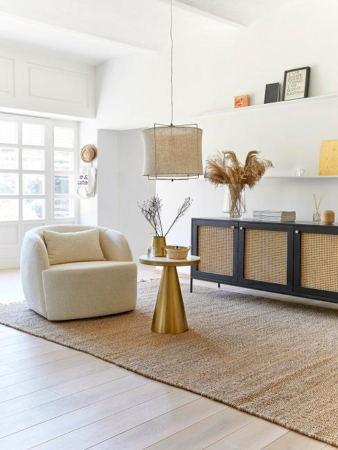 enfilade en cannage dans un salon aux tons naturels, derrière un tapis en sisal avec table basse dorée et un fauteuil en écru.