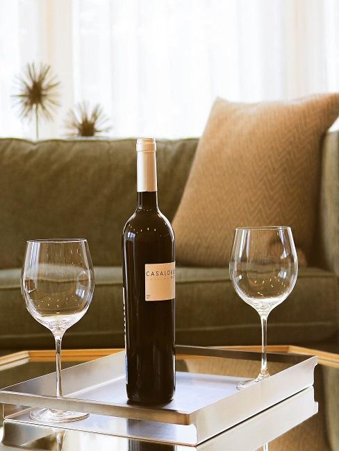 Butelka z winem i dwa kieliszki na tacy stojącej na stoliku kawowym przed sofą