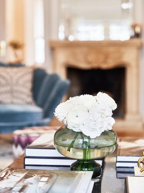 Zielony wazon dekoracyjny wypełniony białymi kwiatami