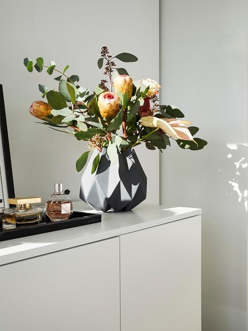 Blumen in grauer Vase auf weißem Sideboard