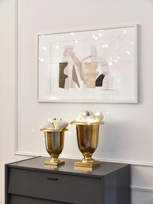 Zwei goldene Pokale stehen im Esszimmer auf einem Sideboard mit weißen Kürbissen und Lichterketten gefüllt.