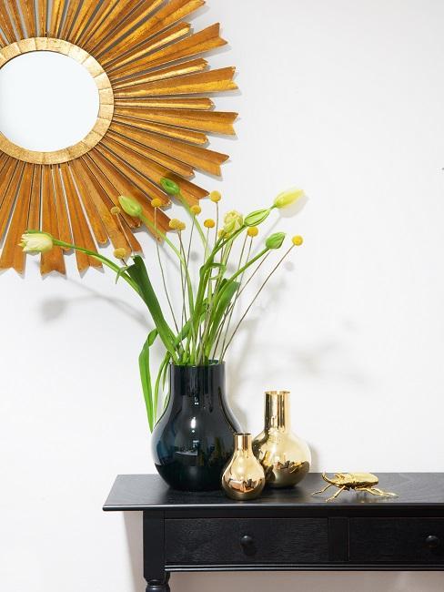cónsola de madera oscura con un jarrón con flores y un espejo en forma de sol