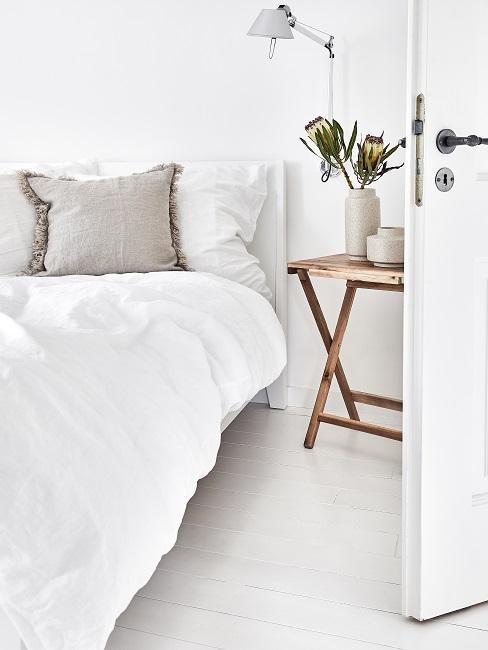 Sypialnia w jasnych barwach z łóżkiem z białą pościelą i drewnianym stolikiem nocnym