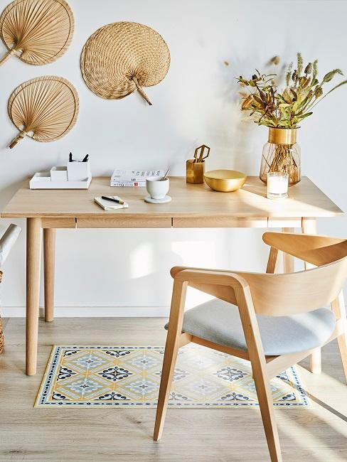 Schreibtisch und Stuhl aus Holz an einer Wand, Rattan-Wandobjekte und eine Vase mit Blumen als Deko