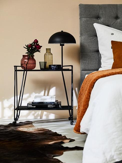 Chariot noir à côté d'un lit gris, sur lequel se trouvent deux vases en verre teinté et d'autres décorations