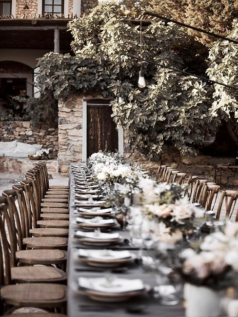Gedekte bruiloftstafel buiten trouwlocatie met veel kaarsen en bloemen als tafeldecoratie in boho stijl