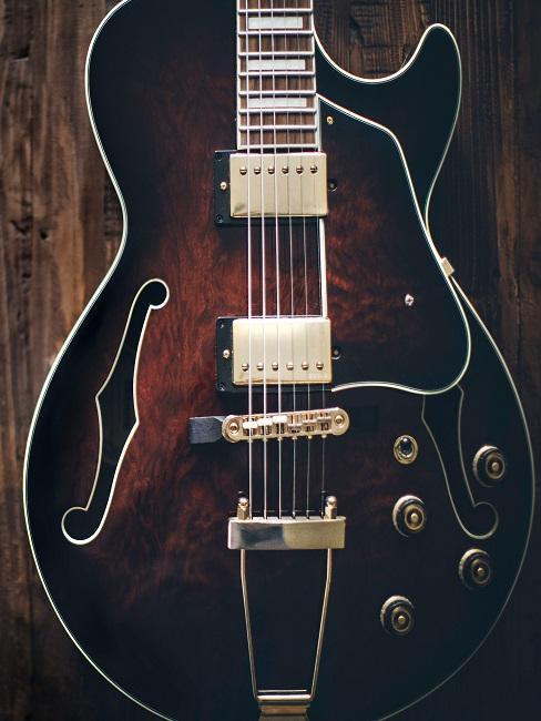 Western Gitarre an eine Holzwand gelehnt