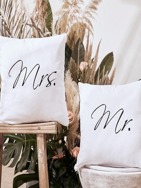 Zwei weiße Kissen mit Mrs und Mr Aufschrift auf einem Holzhocker und einem Topf vor Pflanzendeko