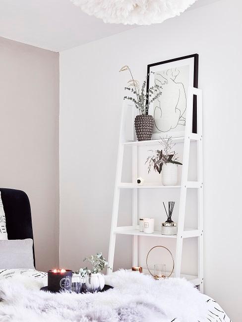 Ein weißes Leiterregal steht im Schlafzimmer an der Wand mit Dekoration.
