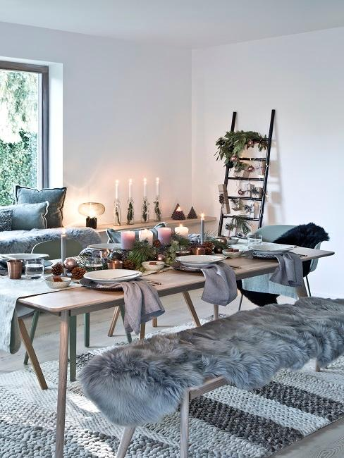 Wohnzimmer mit gedecktem Esstisch, darauf und im Hintergrund weihnachtliche Deko