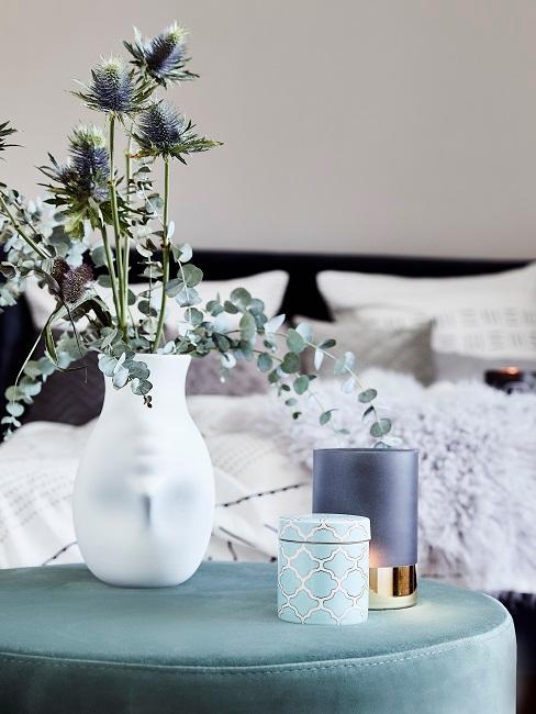 Eukalyptus-Deko als Inspiration in einer weißen Vase auf einem Pouf in Türkis.