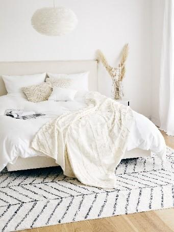Schlafzimmer mit Bett, Kissen, Decke und Teppich in Ecru Farbe