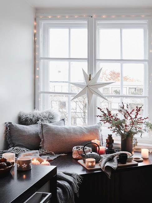 Gemütliche Sitzecke an einem Fenster mit viel Deko wie Kerzen und Kissen, darüber eine Lichterkette
