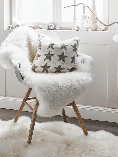 Stuhl mit felliger Auflage und einem Kissen, dahinter ein Fenster mit Kerzen und Weihnachtskugeln als Deko