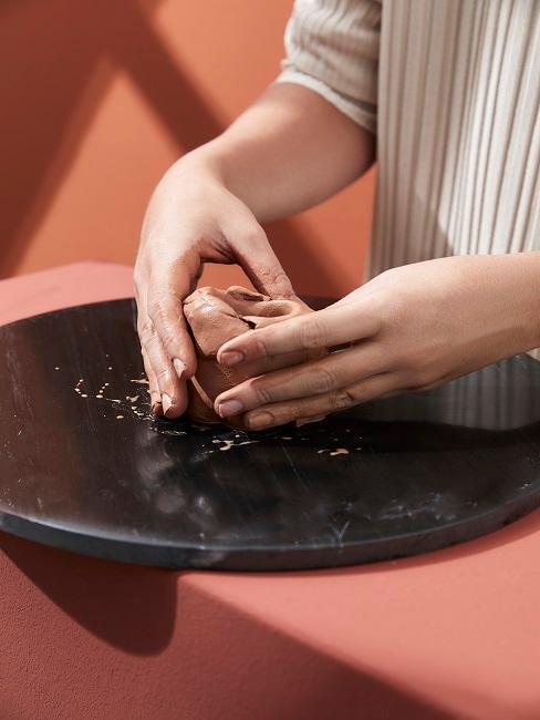 Eine Frau macht Natur-Deko selber mit Knetton in den Händen.