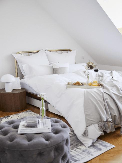 Kleines Schlafzimmer mit Bett, weißer Bettwäsche und Samtsessel