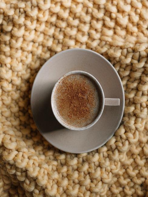 Eine Tasse Cappuccino auf einer hellbraunen Chunky Knit Decke