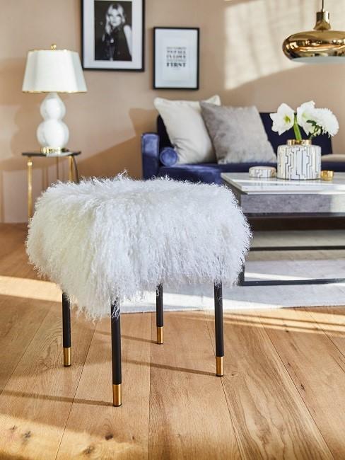 Weißer Fellhocker mit schwarzem Beinen im Wohnzimmer