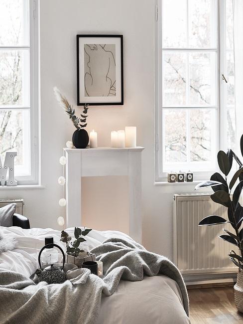 Weiße Kamin-Attrappe dekoriert mit Kerzen und Lichterkette im Schlafzimmer