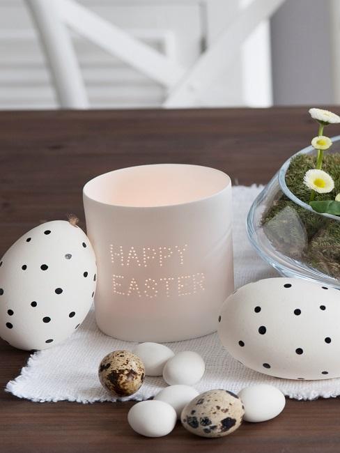 Kerze mit Oster-Spruch neben Ostereiern auf dem Esstisch