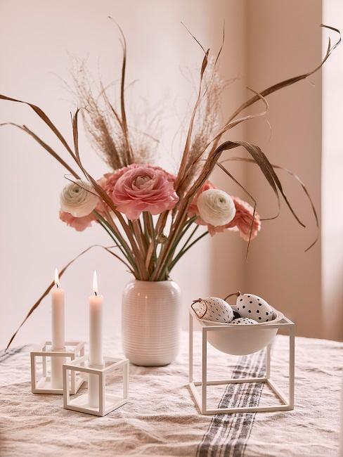 Ostereier in weißer Dekoschale neben Blumen und Kerzen