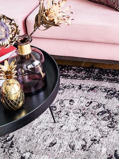 Couchtich mit Deko auf einem Vintage Orient-Teppich vor einem rosa Sofa