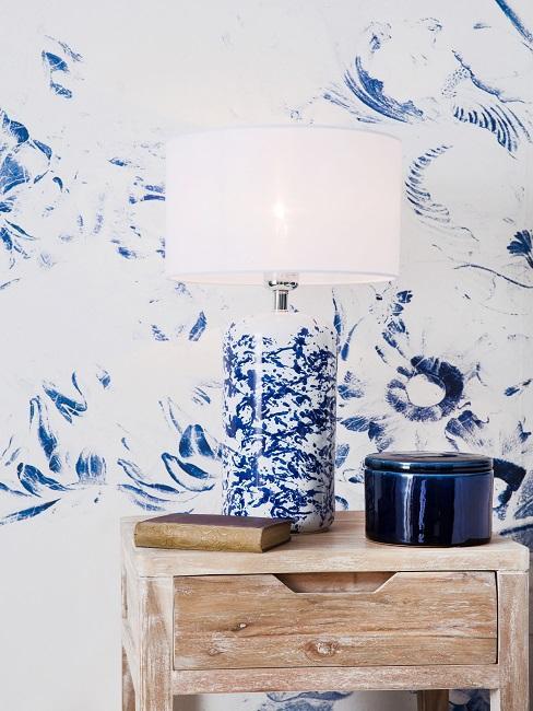 Tapezierte Wand in Blau-Weiß, davor eine kleine Holz-Kommode mit einer Lampe im Vintage Look, ebenfalls in Blau-Weiß