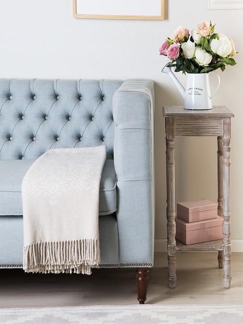 Hellblaues Sofa im Vintage Stil neben einem Shabby Beistelltisch mit nostalgischer Blumendeko