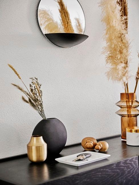 Ablage in Schwarz mit orangenen Vasen und Pampasgras