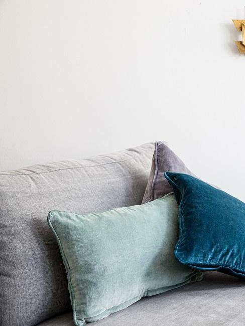 Couch mit Kissen in verschiedenen Grün-Tönen und Grau