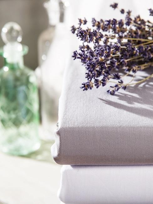 Zusammengefaltete Bettwäsche auf der Ablage mit einem Bund Lavendelzweige.