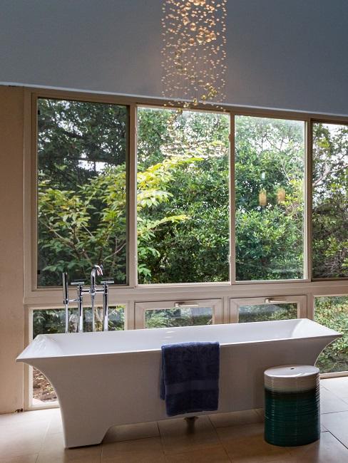 Ein Luxus Badezimmer mit einer freistehenden Badewanne und einer schönen Leuchte an der Decke.