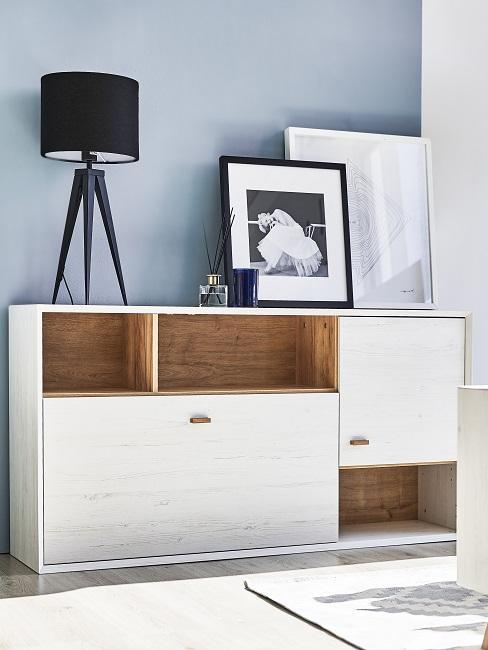 Weiße Kommode mit einer Tischlampe, einem Raumduft und Bildern als Deko