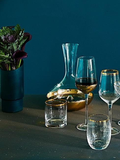 Petrol Wandfarbe hinter Tisch mit Gläsern ud Pflanze