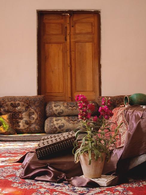 Ein Raum mit vielen Teppichen und Sitzmöglichkeiten im indischen Stil bezüglich Farben und Mustern