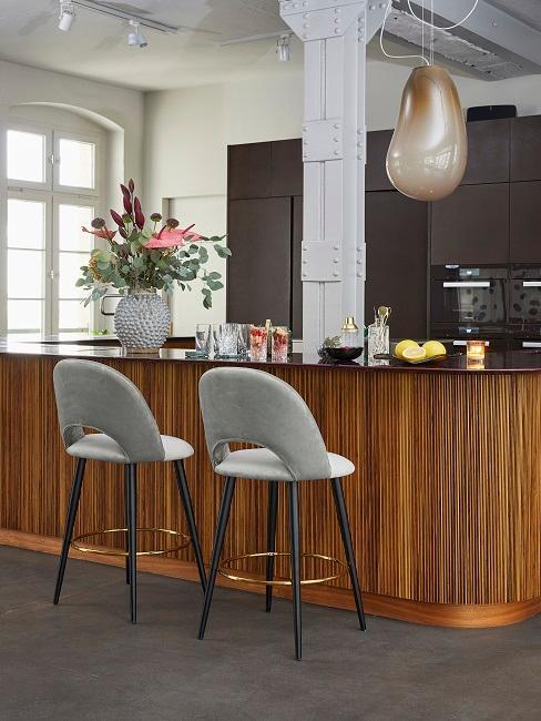 Küchenzeile mit grauen Barhockern und Blumen als Deko