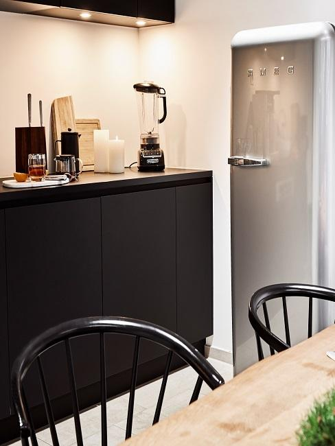Schwarze Küchenzeile neben silbernem Kühlschrank